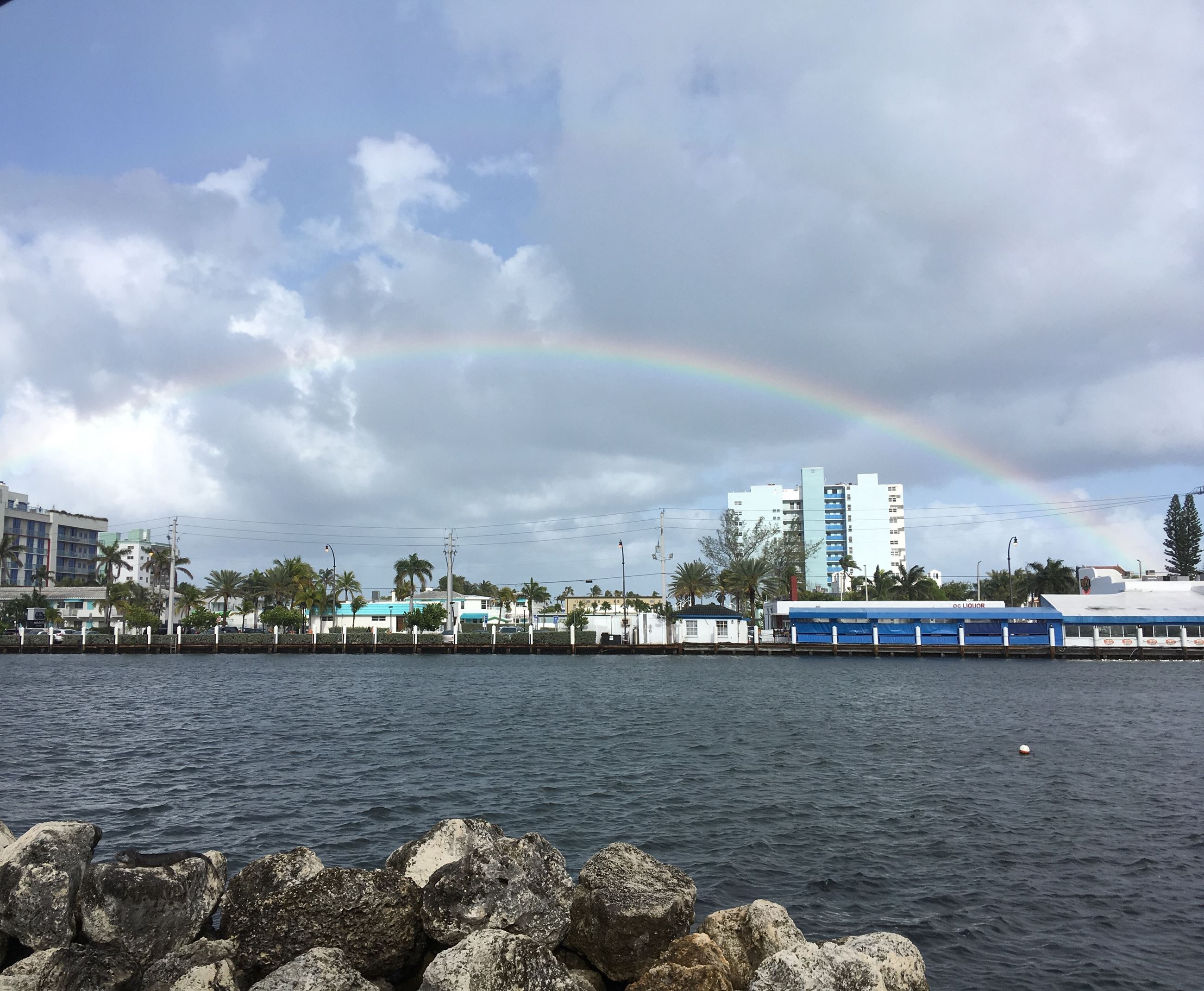 rainbow over the intracoastal water way showing buildings in a row on the other side.